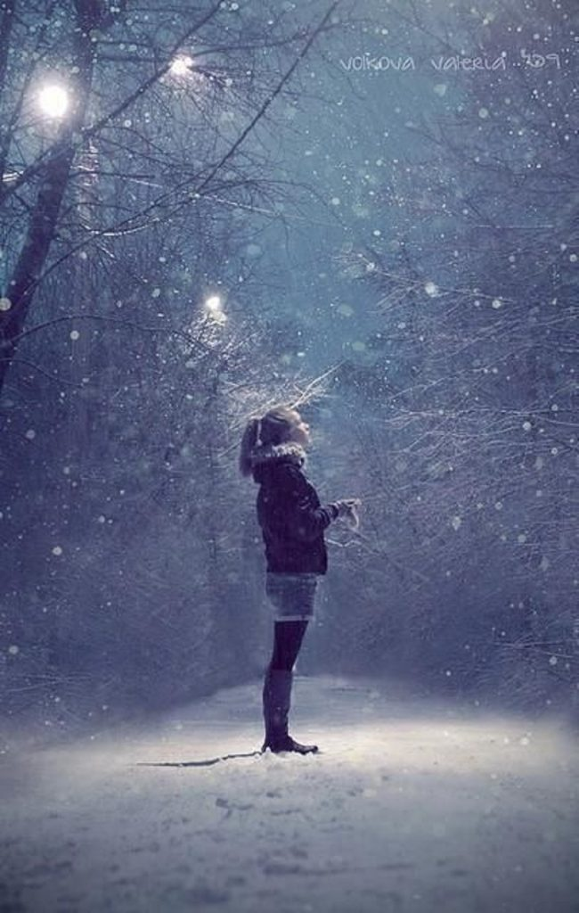 girl looking up at night snowing
